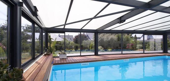 piscine abritée par une véranda en aluminium conçue par Vérancial